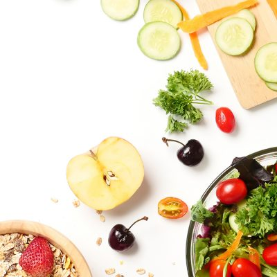 Top view of mixed vegetables salad, muesli and fresh fruits on white background. copy space